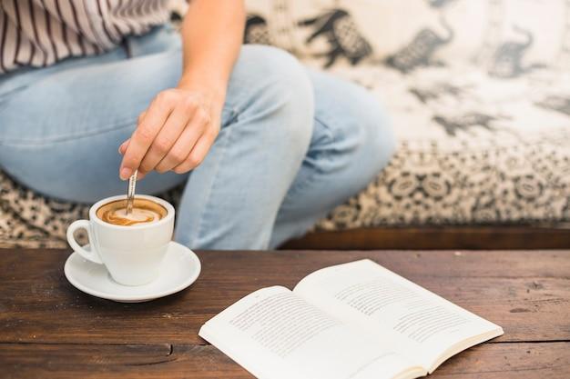 Primo piano della mano della femmina che mescola il latte del caffè con il cucchiaio e libro sulla tavola