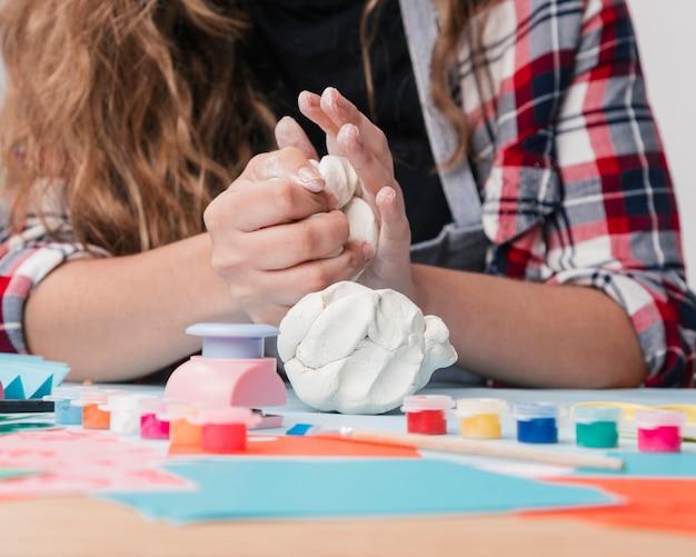 Primo piano della mano della giovane donna che impasta argilla bianca