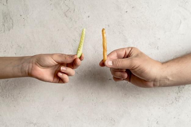 Primo piano della mano della persona che tiene fetta di cetriolo e patatine fritte su sfondo concreto