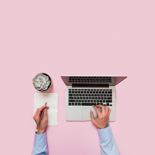 Primo piano della mano della persona di affari che scrive sul computer portatile e che scrive sulla carta con la matita contro fondo rosa