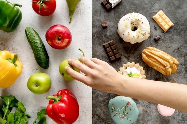 Primo piano della mano della persona prendendo cibo sano