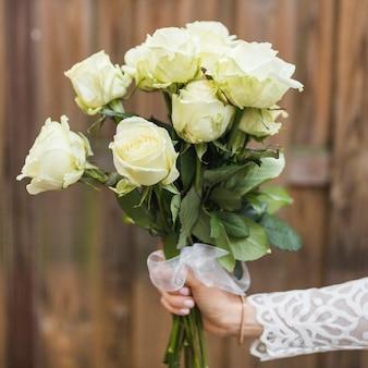 Primo piano della mano della sposa che tiene il mazzo di rose