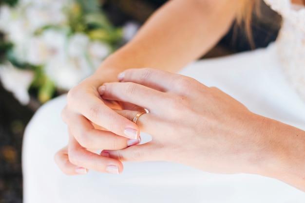 Primo piano della mano della sposa che tocca la sua fede nuziale sul dito
