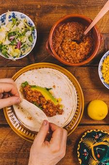 Primo piano della mano delle persone che prepara i tacos del manzo dell'involucro