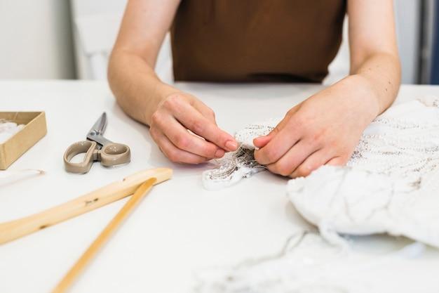 Primo piano della mano dello stilista che lavora sul tessuto sopra workdesk