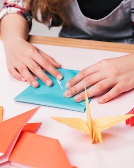 Primo piano della mano di donna pieghevole carta origami per fare mestiere creativo