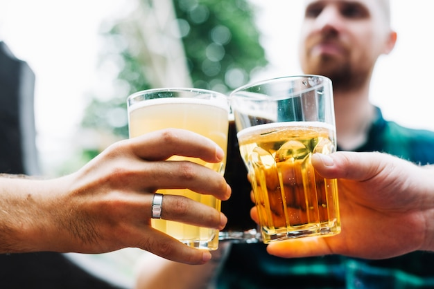 Primo piano della mano di due amici maschii che tostano il vetro di bevande alcoliche