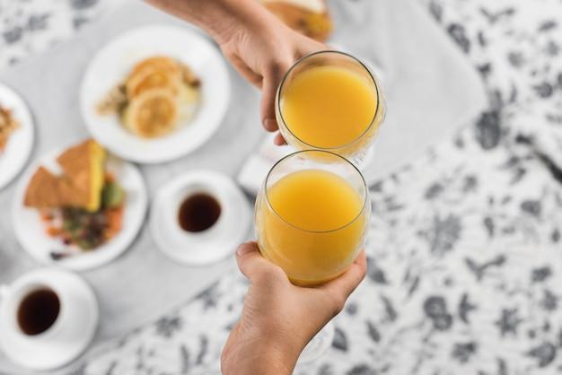 Primo piano della mano di due persone tostatura bicchieri di succo d'arancia