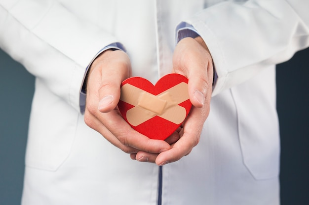 Primo piano della mano di medico che tiene cuore rosso con bende incrociate