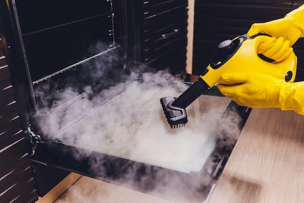Primo piano della mano di pulizia della casa del forno di pulizia a vapore.