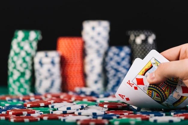 Primo piano della mano di un giocatore che gioca a poker nel casinò