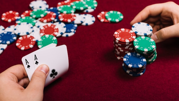 Primo piano della mano di un giocatore di poker con carte da gioco e fiches