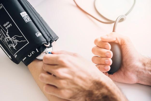 Primo piano della mano di un medico che controlla pressione sanguigna del paziente