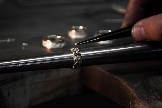 Primo piano della mano di un orafo che fissa il diamante sull'anello. creazione di gioielli artigianali con strumenti professionali.