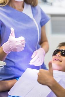 Primo piano della mano di un ragazzo e del dentista che gesturing i pollici su