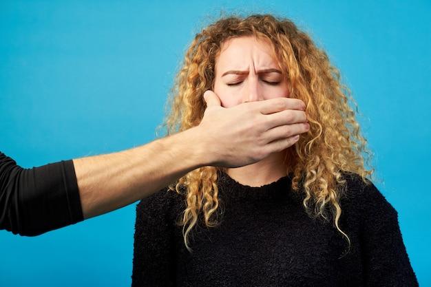 Primo piano della mano di un uomo che copre la bocca di una giovane ragazza bella rossa o donna.