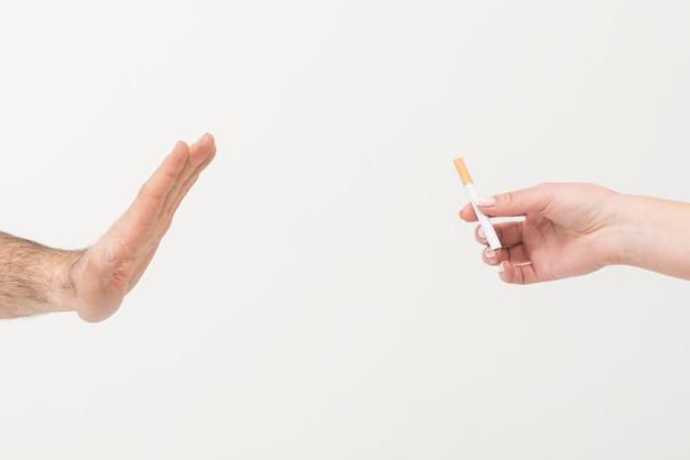 Primo piano della mano di un uomo che dice no alla sigaretta data da una persona isolata sul contesto bianco