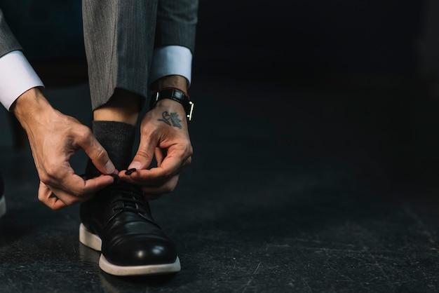 Primo piano della mano di un uomo che lega i lacci delle scarpe