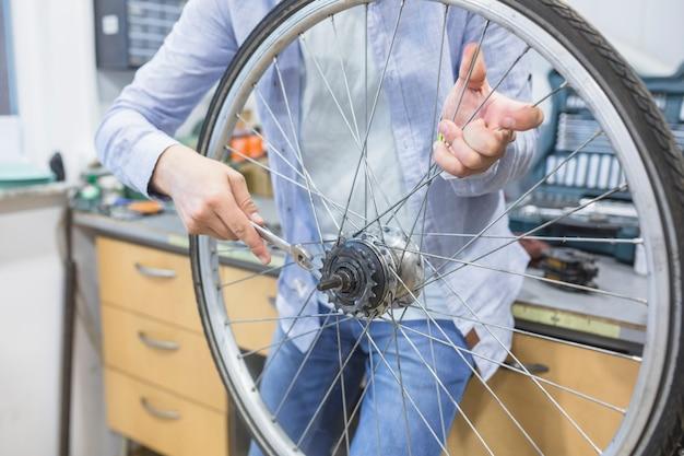 Primo piano della mano di un uomo che ripara la gomma della bicicletta con la chiave