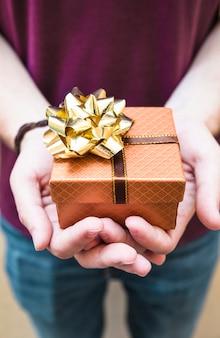 Primo piano della mano di un uomo che tiene il regalo di san valentino