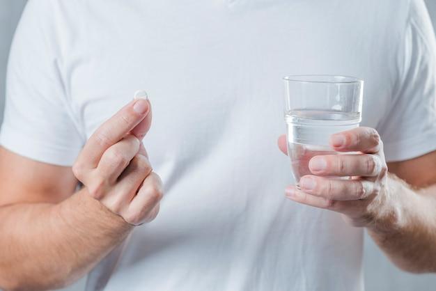 Primo piano della mano di un uomo che tiene in mano bianco pillola e bicchiere d'acqua