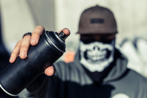 Primo piano della mano di un uomo che tiene la bomboletta spray nera