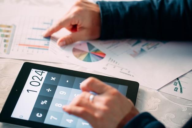 Primo piano della mano di un uomo d'affari che analizza bill sulla tavoletta digitale sopra la scrivania,