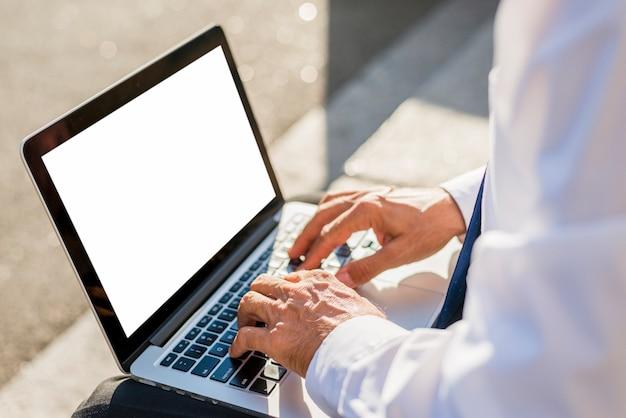 Primo piano della mano di un uomo d'affari utilizzando il computer portatile con schermo bianco vuoto