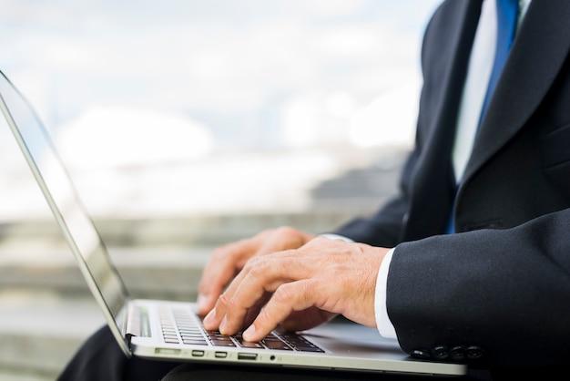 Primo piano della mano di un uomo d'affari utilizzando il computer portatile
