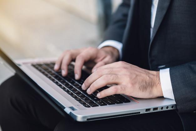 Primo piano della mano di un uomo in un vestito. stampa sulla tastiera di un laptop mentre sei seduto sui gradini