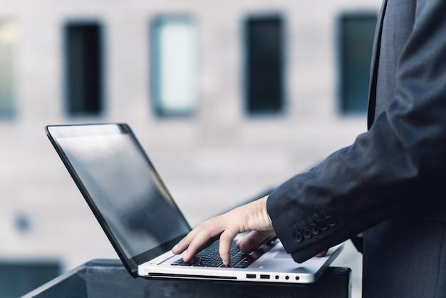 Primo piano della mano di un uomo in un vestito. stampa sulla tastiera di un laptop