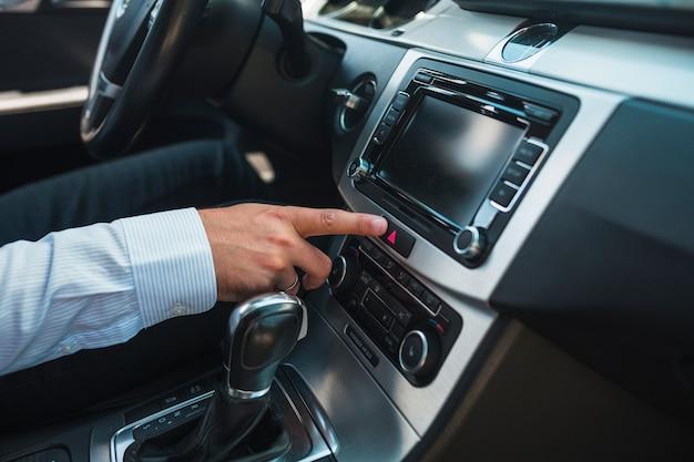Primo piano della mano di un uomo utilizzando l'impianto stereo dell'auto