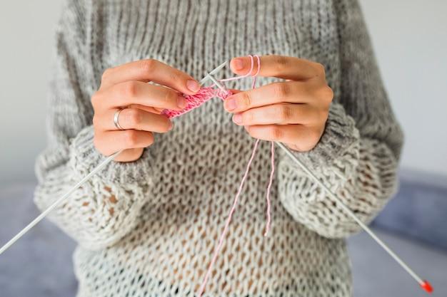 Primo piano della mano di una donna a maglia con uncinetto