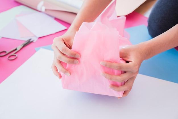 Primo piano della mano di una donna che avvolge carta rosa sul contenitore di regalo