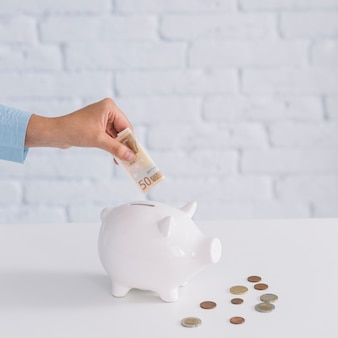 Primo piano della mano di una donna che inserisce una banconota da cinquanta euro nel porcellino salvadanaio sullo scrittorio