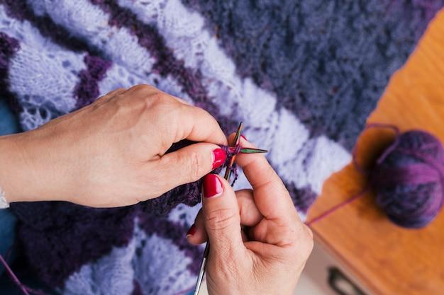 Primo piano della mano di una donna che lavora a maglia la sciarpa