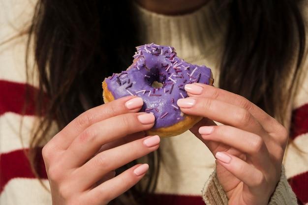 Primo piano della mano di una donna che mangia ciambella porpora