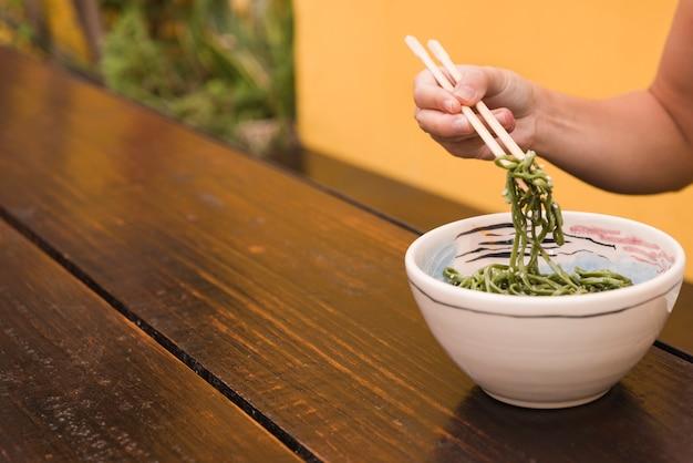 Primo piano della mano di una donna che mangia l'alga del chuka del sesamo con le bacchette