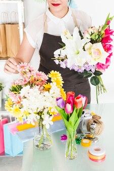 Primo piano della mano di una donna che ordina i fiori in vaso