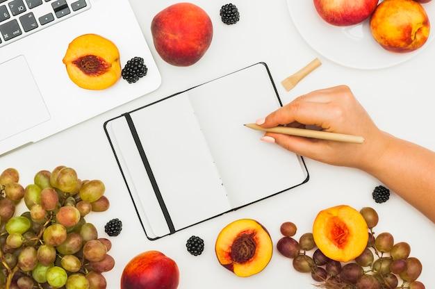 Primo piano della mano di una donna che scrive sul diario con frutta e laptop sul tavolo bianco