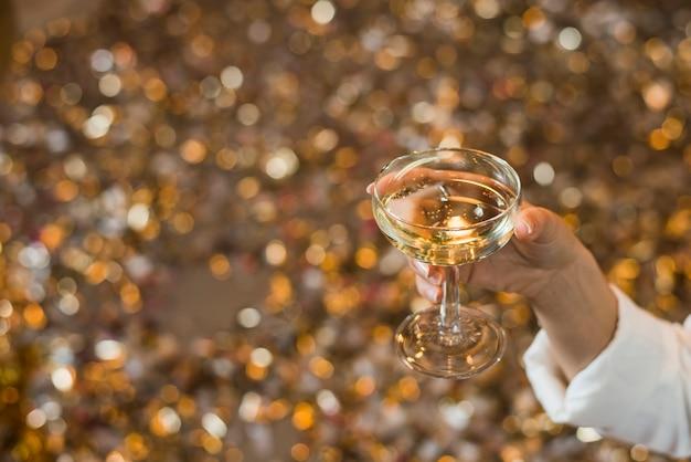 Primo piano della mano di una donna che tiene bicchiere di whisky