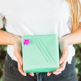 Primo piano della mano di una donna che tiene il contenitore di regalo di compleanno verde