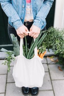Primo piano della mano di una donna che tiene la borsa di cotone con verdure