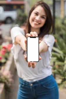 Primo piano della mano di una donna che tiene smartphone con schermo bianco vuoto