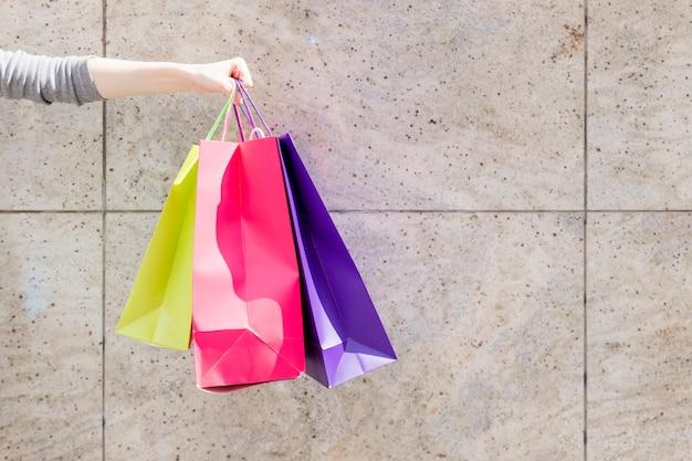 Primo piano della mano di una donna con i sacchetti della spesa variopinti davanti alla parete