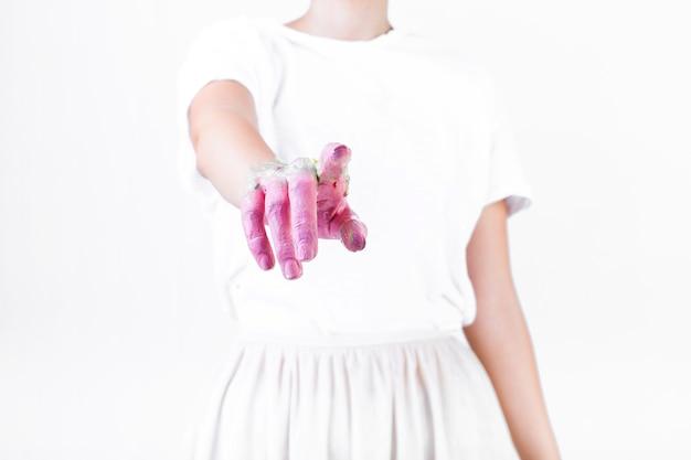 Primo piano della mano di una donna con la vernice rosa che punta il dito