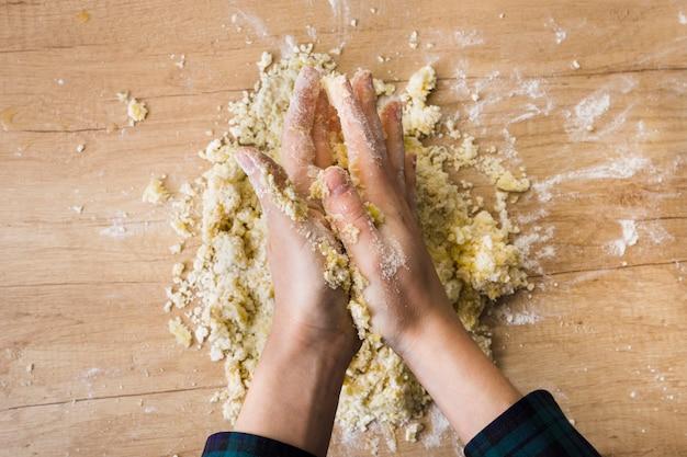 Primo piano della mano di una donna impastando la pasta per la preparazione di gnocchi italiani sulla scrivania in legno