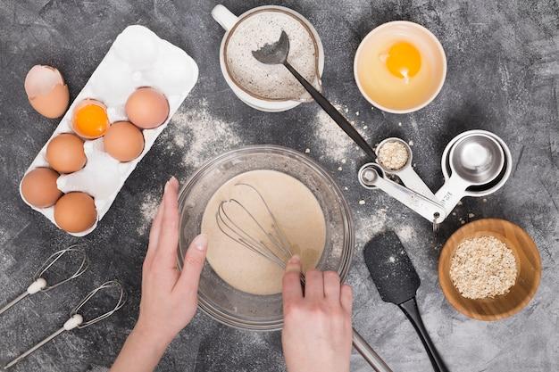 Primo piano della mano di una femmina che prepara gli ingredienti del pane sul contesto concreto