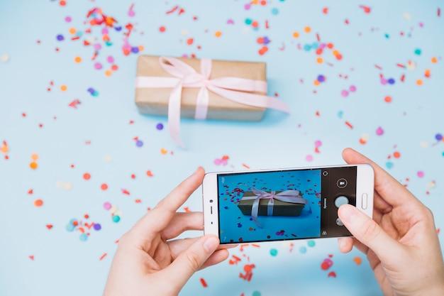 Primo piano della mano di una persona che cattura foto del contenitore di regalo sullo smart phone