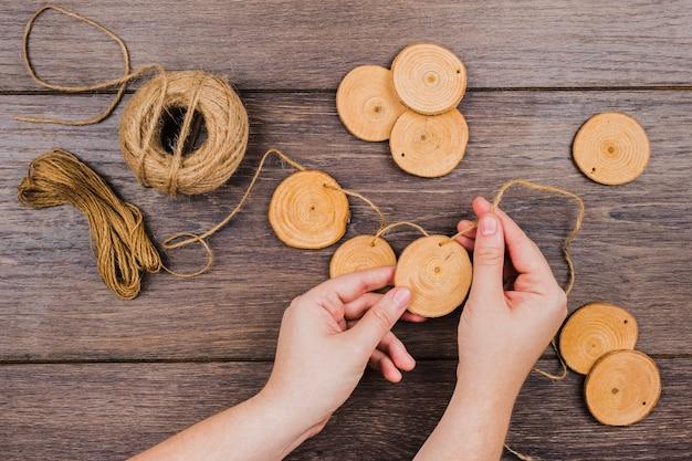 Primo piano della mano di una persona che fa ghirlanda con anello in legno e filo sulla tavola di legno